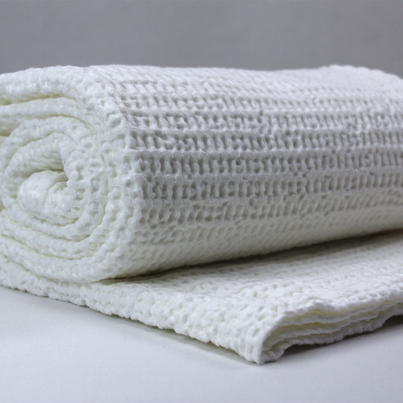 White honeycomb design blanket pictured rolled up on on grey background