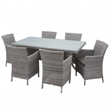 Six seater grey rattan garden table and chairs in front of stone wall