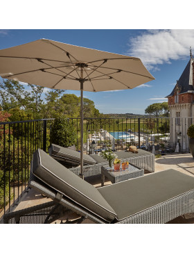 Two rattan sun loungers and a coffee table and parasol  on a southern French terrace overlooking a chateau and a pool
