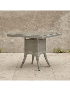 Four seater grey rattan garden table at an angle in front of stone wall