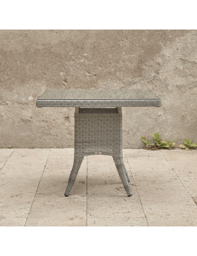 side view of four seater grey rattan garden table in front of stone wall