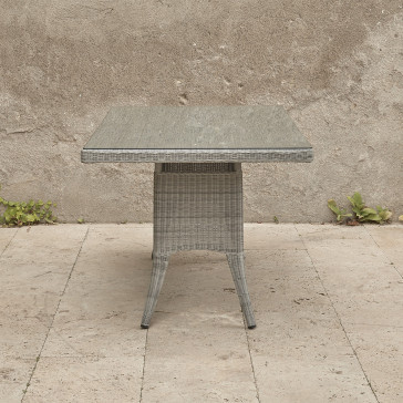 Six seater grey rattan garden table in front of stone wall view from end of table