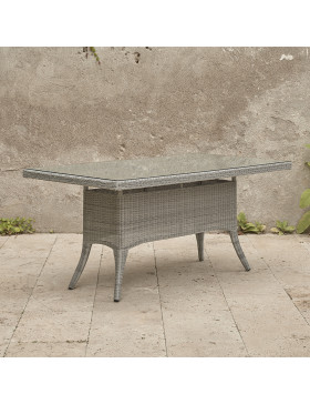 Six seater grey rattan garden table on an angle in front of stone wall