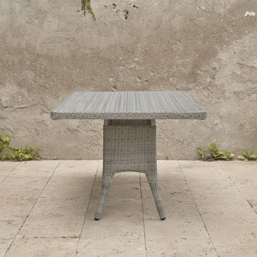 Eight seater grey rattan garden table in front of stone wall image from end of table