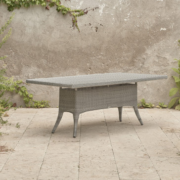 Eight seater grey rattan garden table at an angle in front of stone wall