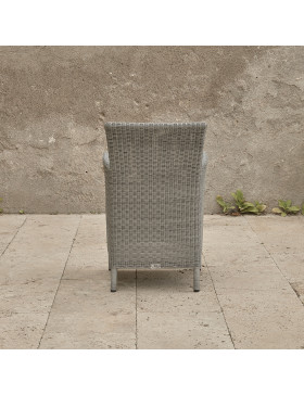Grey rattan dining chair. On a terrace in front of stone wall back view