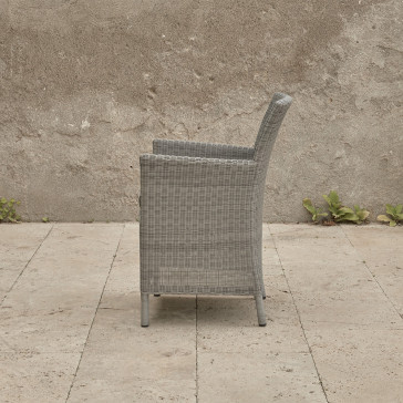 Grey rattan dining chair. On a terrace in front of stone wall side view