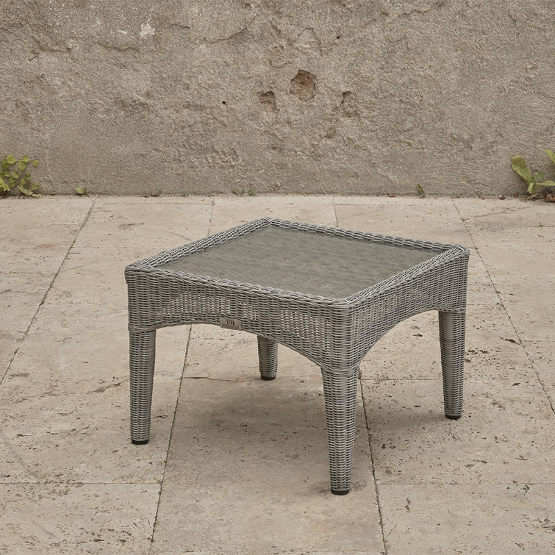 Compact garden rattan side table wirh tempered glass top pictured at an angle on a southern French terrace