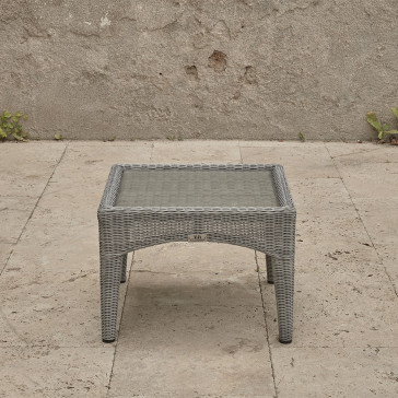 Compact garden rattan side table wirh tempered glass top pictured from the side on a southern French terrace