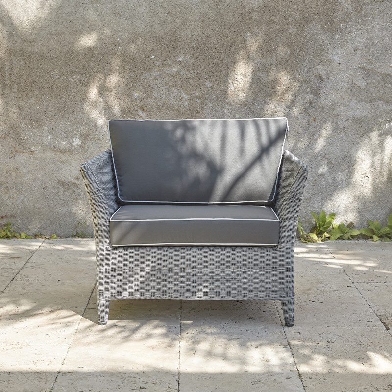 Durable and elegant rattan garden armchair in French grey with UV resistant cushions on a southern French terrace