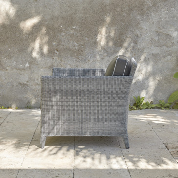 Durable and elegant rattan garden armchair side view in French grey with UV resistant cushions on a southern French terrace