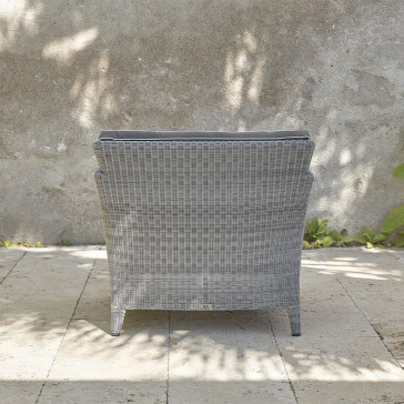 Durable and elegant rattan garden armchair back view in French grey with UV resistant cushions on a southern French terrace