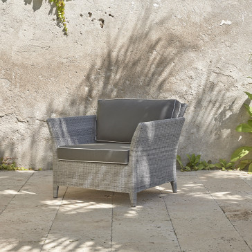Durable and elegant rattan garden armchair at an angle in French grey with UV resistant cushions on a southern French terrace
