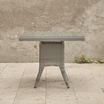 Four seater Grey rattan garden table. On a terrace in front of stone wall
