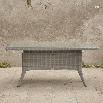 Six seater Grey rattan garden table. On a terrace in front of stone wall