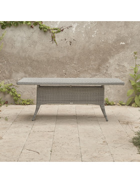 Eight seater Grey rattan garden table. On a terrace in front of stone wall