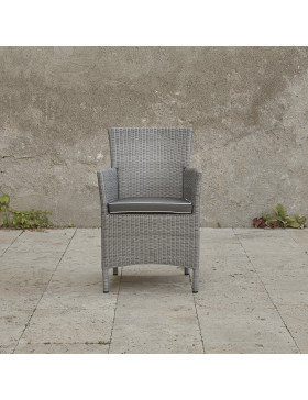 Grey rattan dining chair. On a terrace in front of stone wall