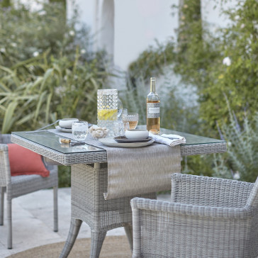 Two seater table and chairs. French Grey rattan. In a French garden.