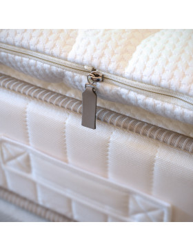 Close up of Mattress Topper with zip opening on bed with mattress.