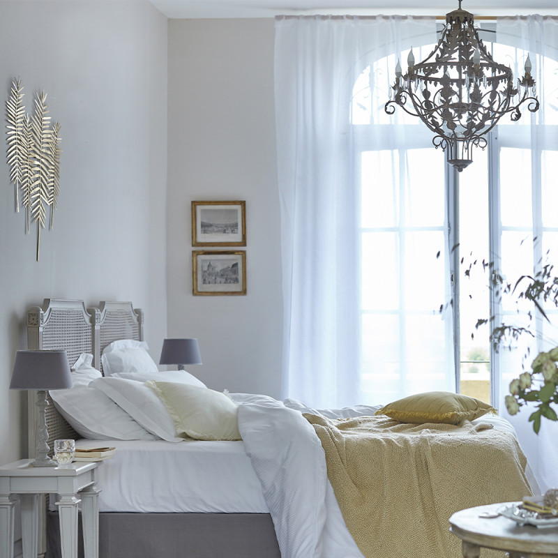 Bed with crisp white bed linen, yellow throw and cushion in a classic French bedroom with chandelier