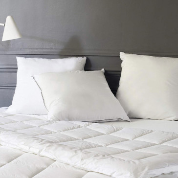three pillows on a bed with quilted white duvet