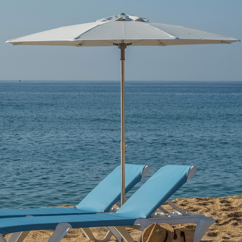 octagonal shaped parasol fully opened on french beach next to blue ocean