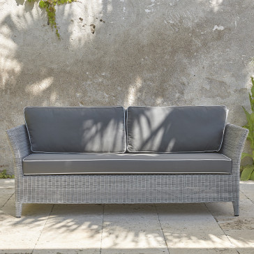 Two-seater rattan couch with UV resistant cushions in French grey on a southern French terrace