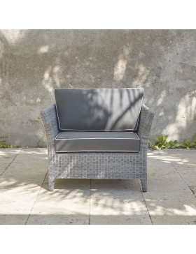 Durable and elegant garden armchair in french grey with UV resistant cushions and pale grey offset piping on a French terrace