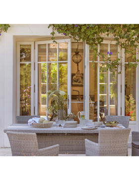 Six seater table and chairs. French Grey rattan. On a French terrace.