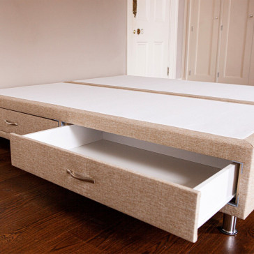 Divan bed base showing both drawers with one drawer open upholstered in an oatmeal furniture fabric pictured on a wooden floor