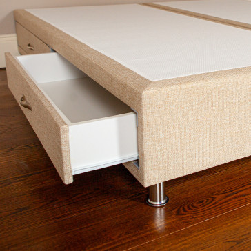 Divan bed base with drawer open upholstered in an oatmeal furniture fabric pictured on a wooden floor