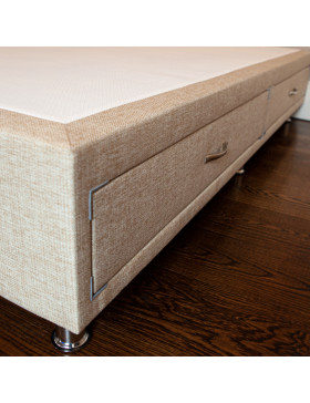 Divan bed base with drawers upholstered in an oatmeal furniture fabric pictured on a wooden floor